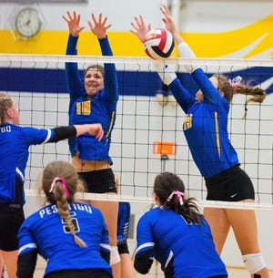 Oconto's Hannah Moe and Cora Behnke block an attack in the first game in their match with Peshtigo on Thursday, Oct. 4.