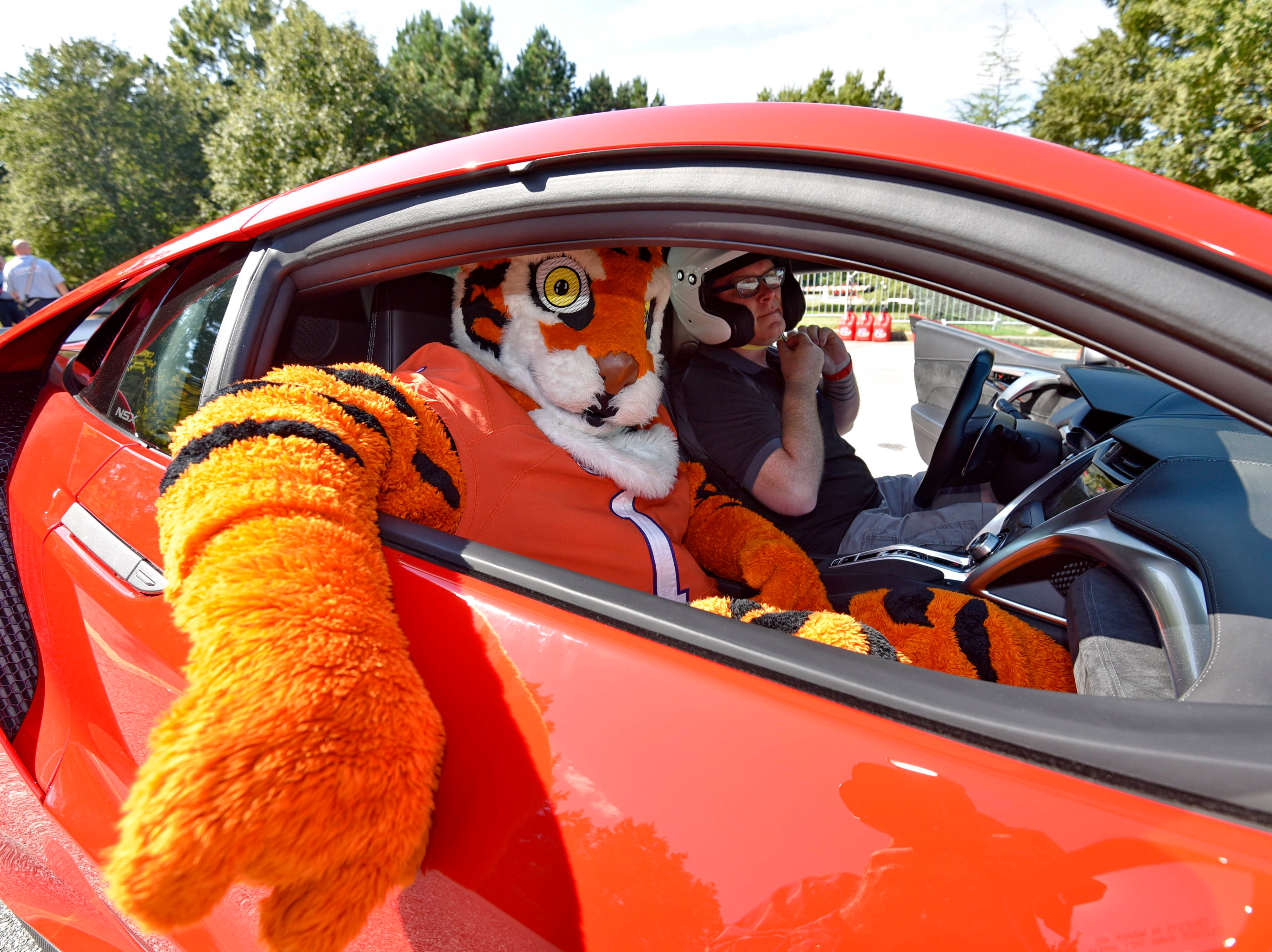 """Professional driver for Honda, Dennis Grisez takes Clemson mascot """"Tiger"""" out for a hot lap. CU-ICAR unveiled the new Deep Orange 9 rally car Saturday, October 6,  2018."""