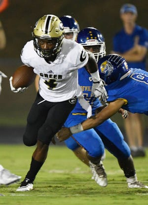 Greer's Cameron Martin (4) eludes the grasp of Travelers Rest's Brooks Russ-Martin (8) during the visiting Yellow Jackets' 58-6 win Friday at Chico Bolin Stadium.
