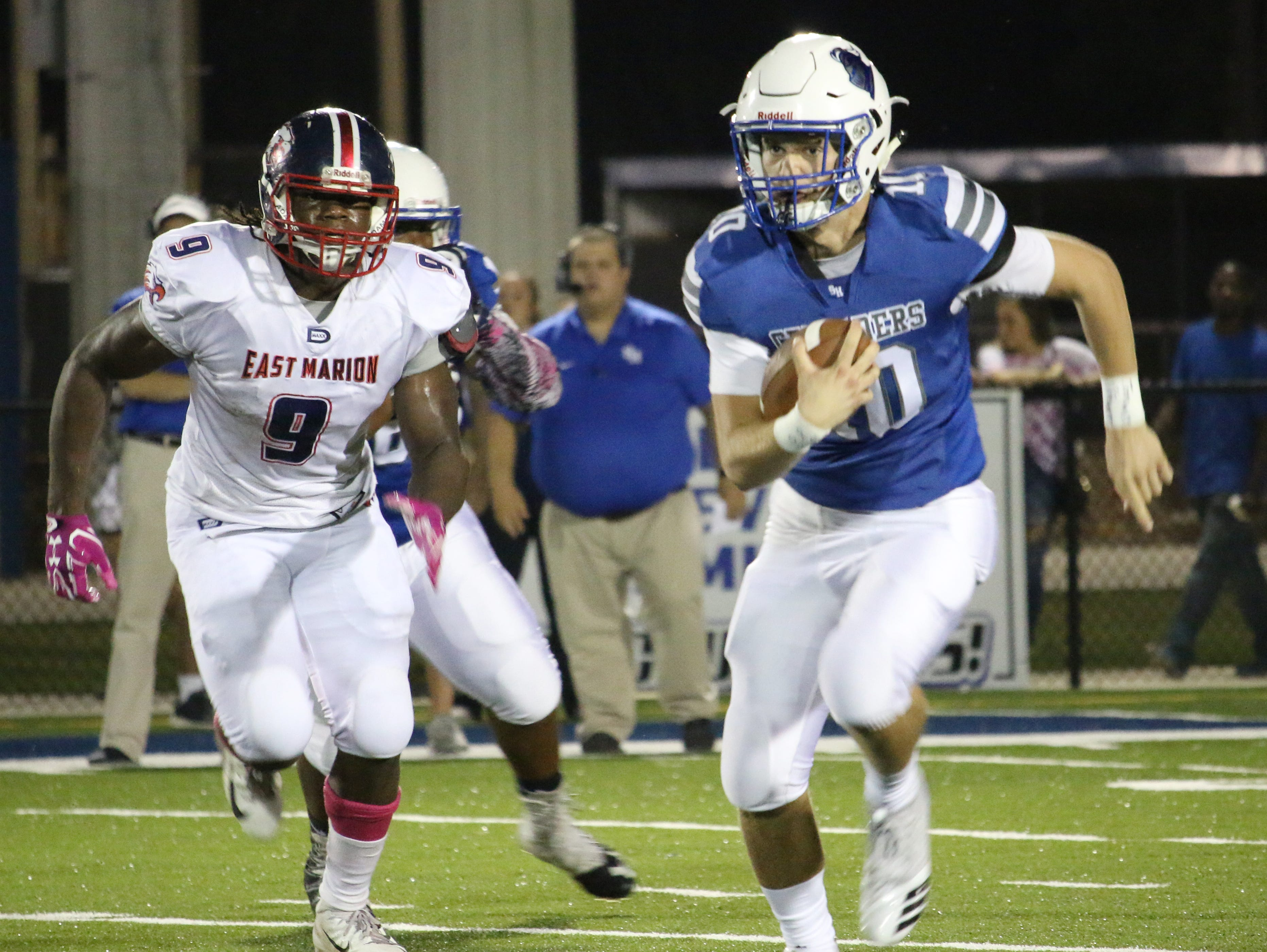 Sacred Heart's QB Zach Weatherell runs with the ball against East Marion on Friday.