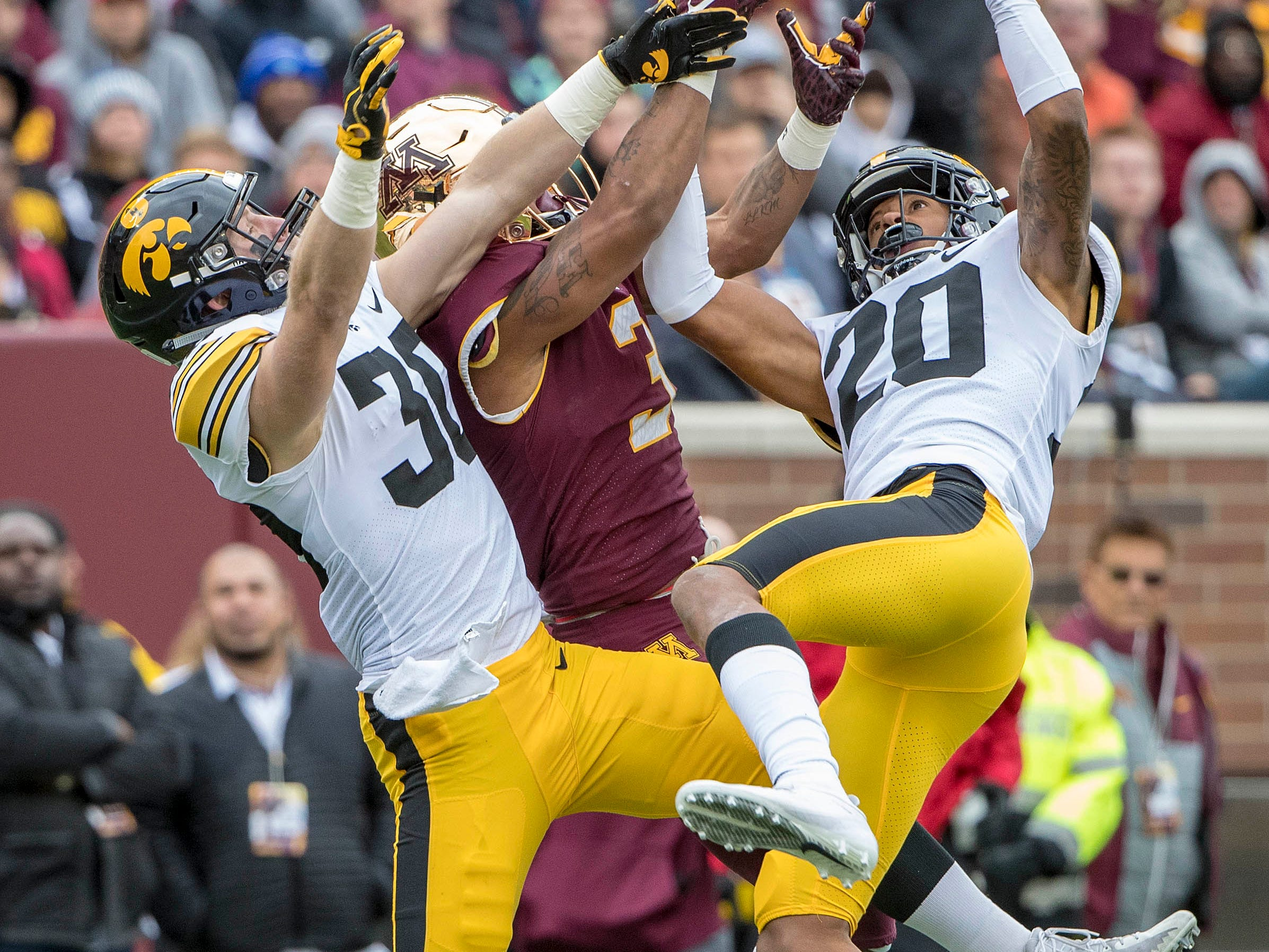 Oct 6, 2018; Minneapolis, MN, USA; Minnesota Golden Gophers wide receiver Chris Autman-Bell (3) and Iowa Hawkeyes defensive back Jake Gervase (30) and defensive back Julius Brents (20) battle for a pass in the first half at TCF Bank Stadium. Mandatory Credit: Jesse Johnson-USA TODAY Sports