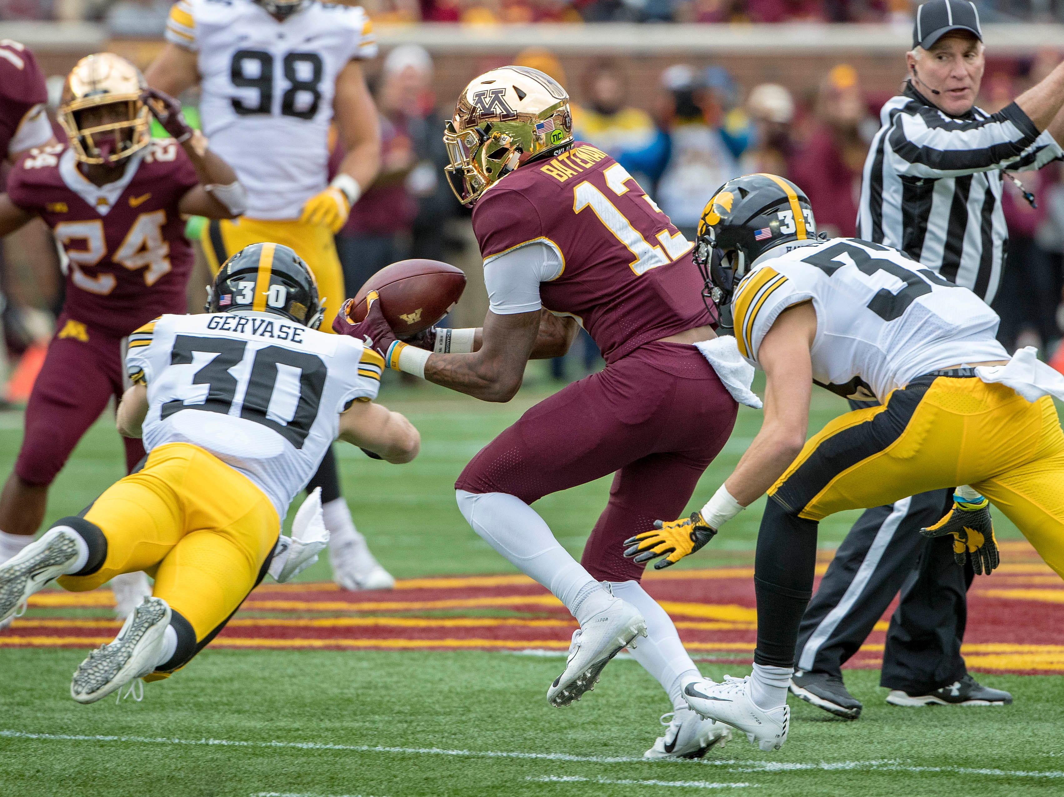 Oct 6, 2018; Minneapolis, MN, USA; Minnesota Golden Gophers wide receiver Rashod Bateman (13) catches a tipped pass in between defense from Iowa Hawkeyes defensive back Jake Gervase (30) and defensive back Riley Moss (33) in the first half at TCF Bank Stadium. Mandatory Credit: Jesse Johnson-USA TODAY Sports