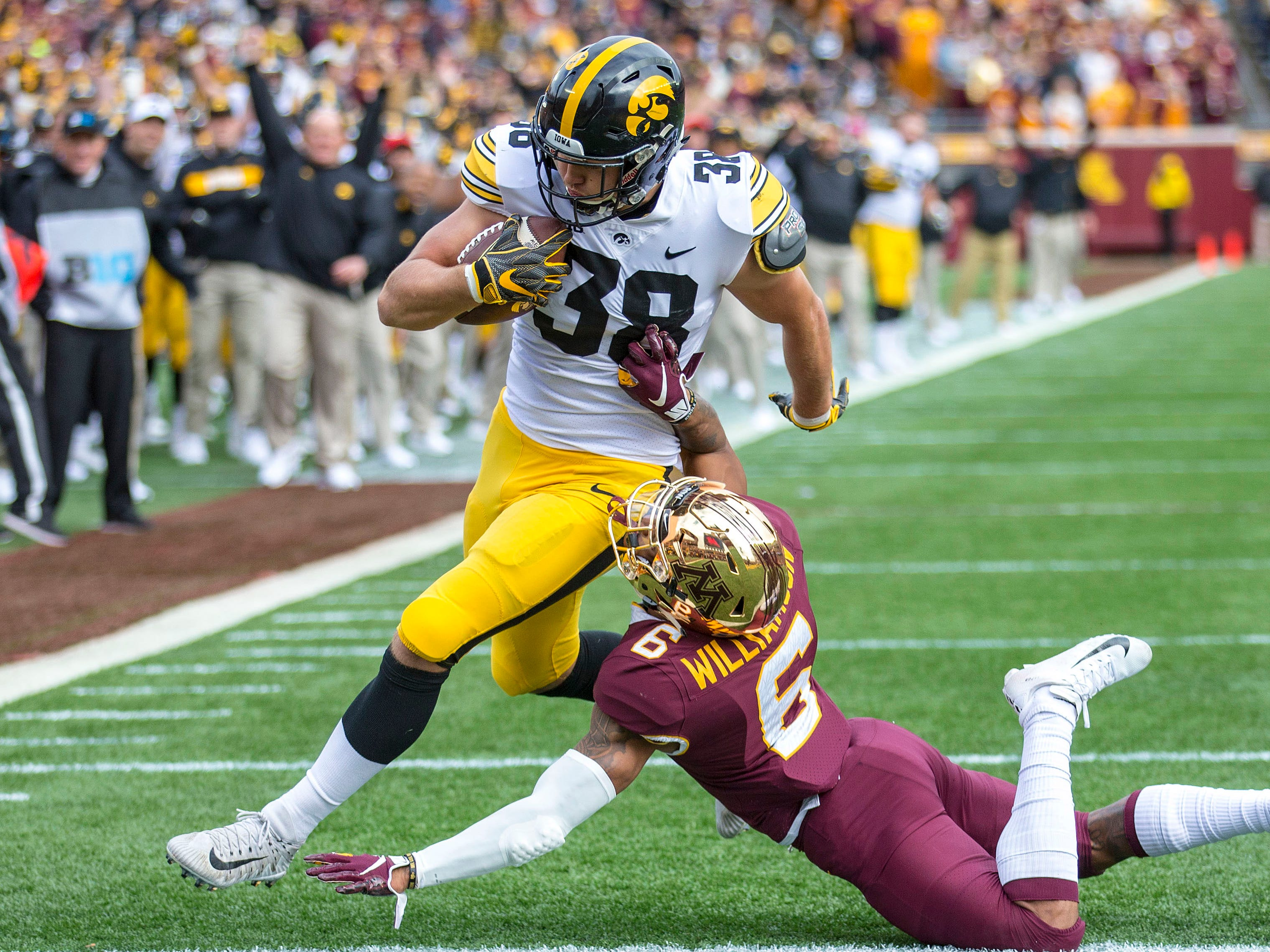 Oct 6, 2018; Minneapolis, MN, USA; Iowa Hawkeyes tight end T.J. Hockenson (38) rushes for a touchdown on a fake field goal attempt against Minnesota Golden Gophers defensive back Chris Williamson (6) in the first half at TCF Bank Stadium. Mandatory Credit: Jesse Johnson-USA TODAY Sports