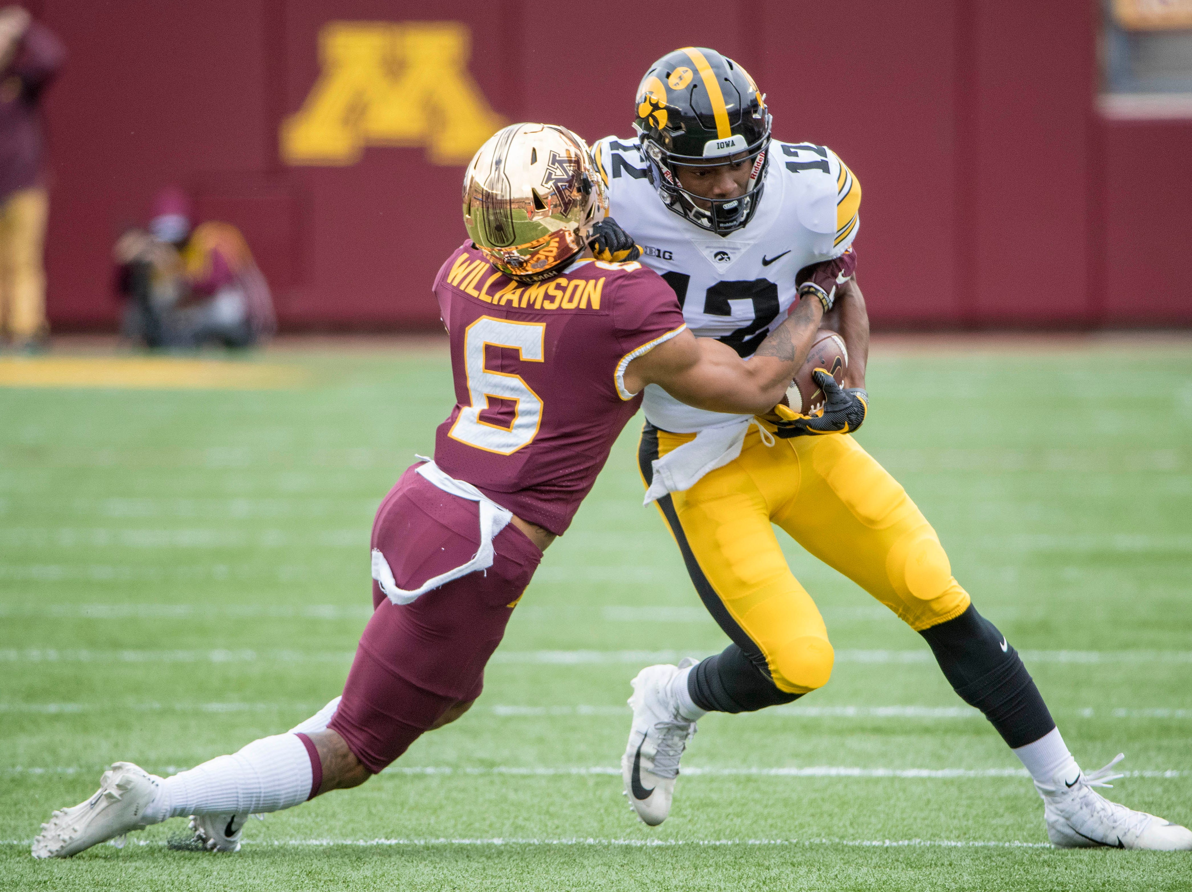 Oct 6, 2018; Minneapolis, MN, USA; Iowa Hawkeyes wide receiver Brandon Smith (12) pushes for a first down after catching a pass against Minnesota Golden Gophers defensive back Chris Williamson (6) in the first quarter at TCF Bank Stadium. Mandatory Credit: Jesse Johnson-USA TODAY Sports