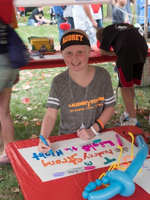 Audrey Wampler decorates a poster at the 2017 Light the Night walk organized by the Indiana Chapter of the Leukemia and Lymphoma Society. Indiana LLS organizer Kathy Pelletier said after seeing this photo she was moved to find Audrey and learn about her battle with cancer.