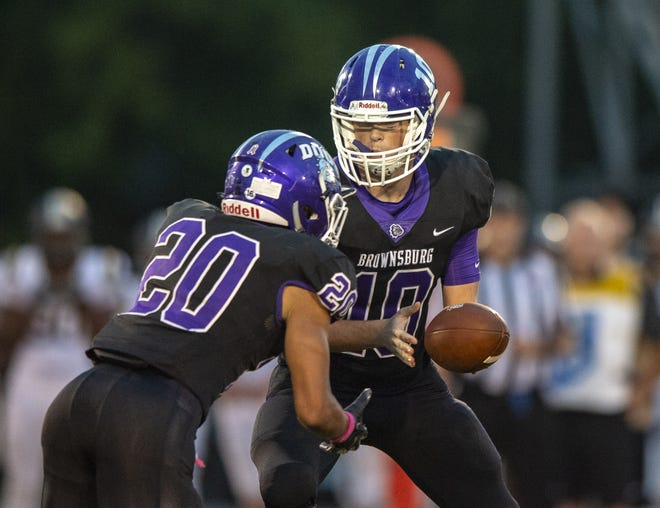 Brownsburg High School sophomore Ben Easters (10) hands the ball off to junior Donny Marcus (20) during the first half of action. Brownsburg High School hosted Noblesville High School in IHSAA varsity football action, Friday, Oct. 5, 2018.