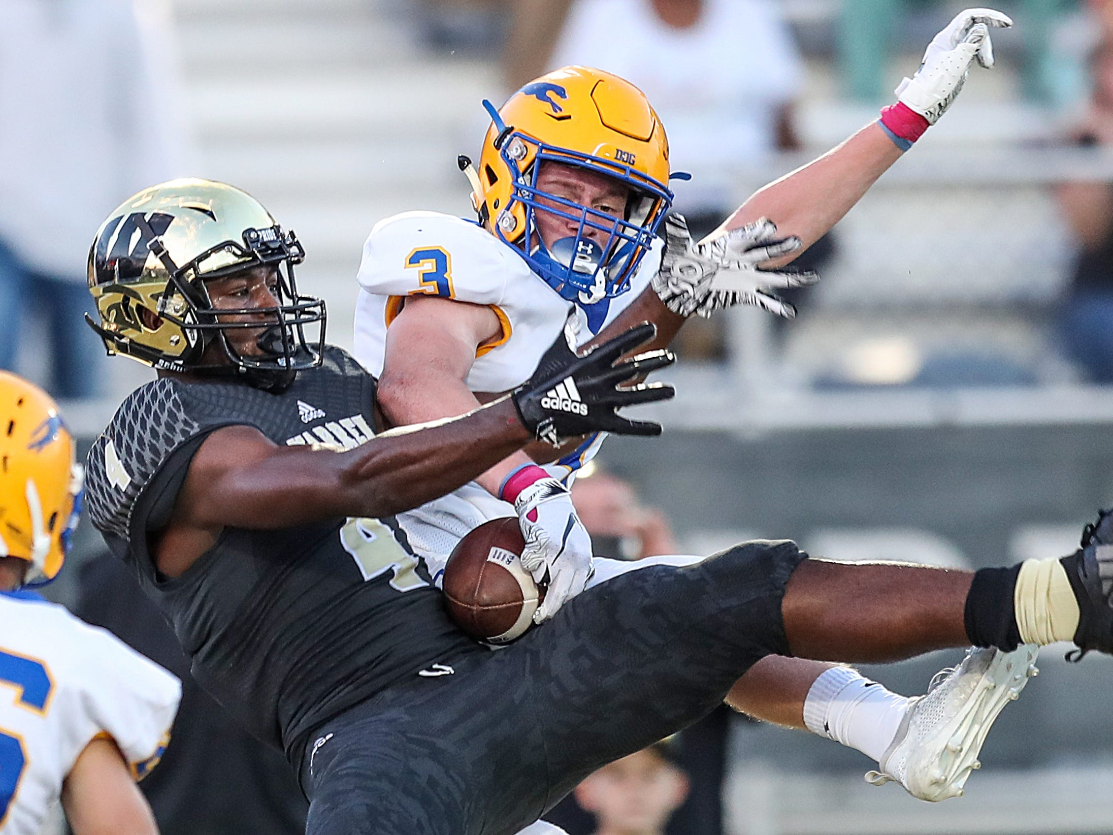 In an attempt to knock it away, Carmel Greyhounds cornerback Jake Paris (3) presses the ball against Warren Central Warriors wide receiver David Bell (4) who keeps it to score the Warriors' first touchdown of the game, in the first half of the game at Warren Central High School, Indianapolis, Ind., Friday, Oct. 5, 2018.