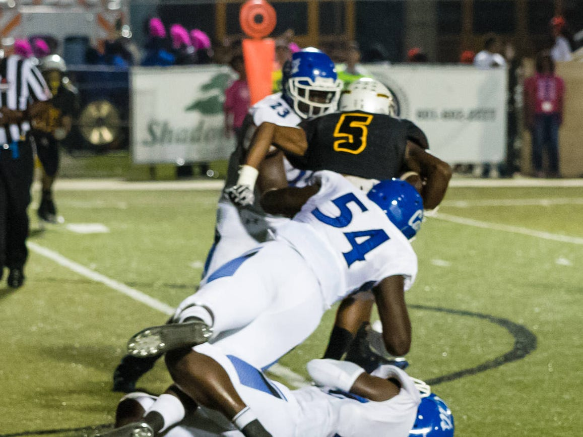 Wildcats defensive players struggle to take down Oak Grove's Tavion Smith (#5).