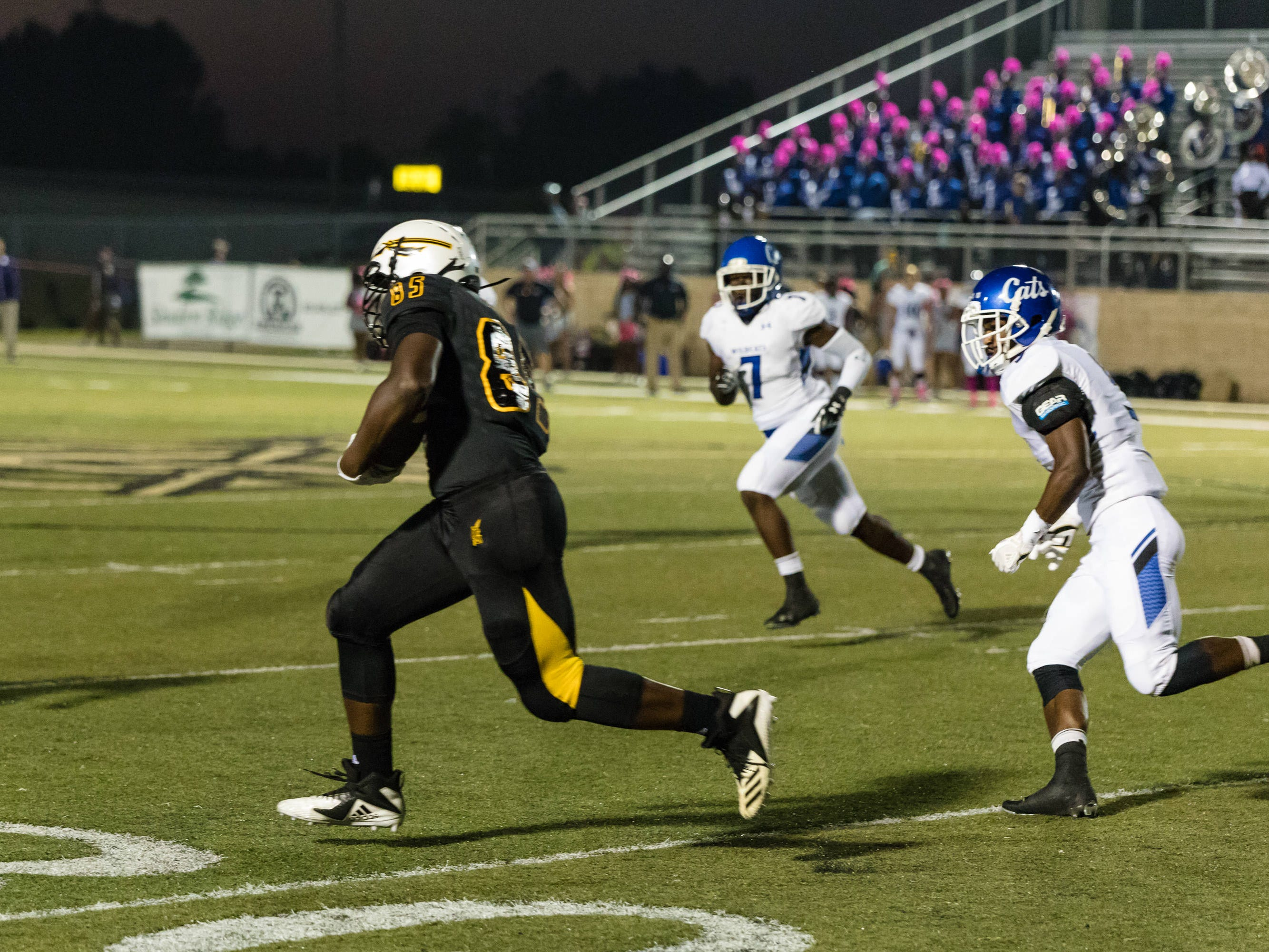 Rasaiah Ruffin (#85) races downfield while pursued by Meridian Wildcats.