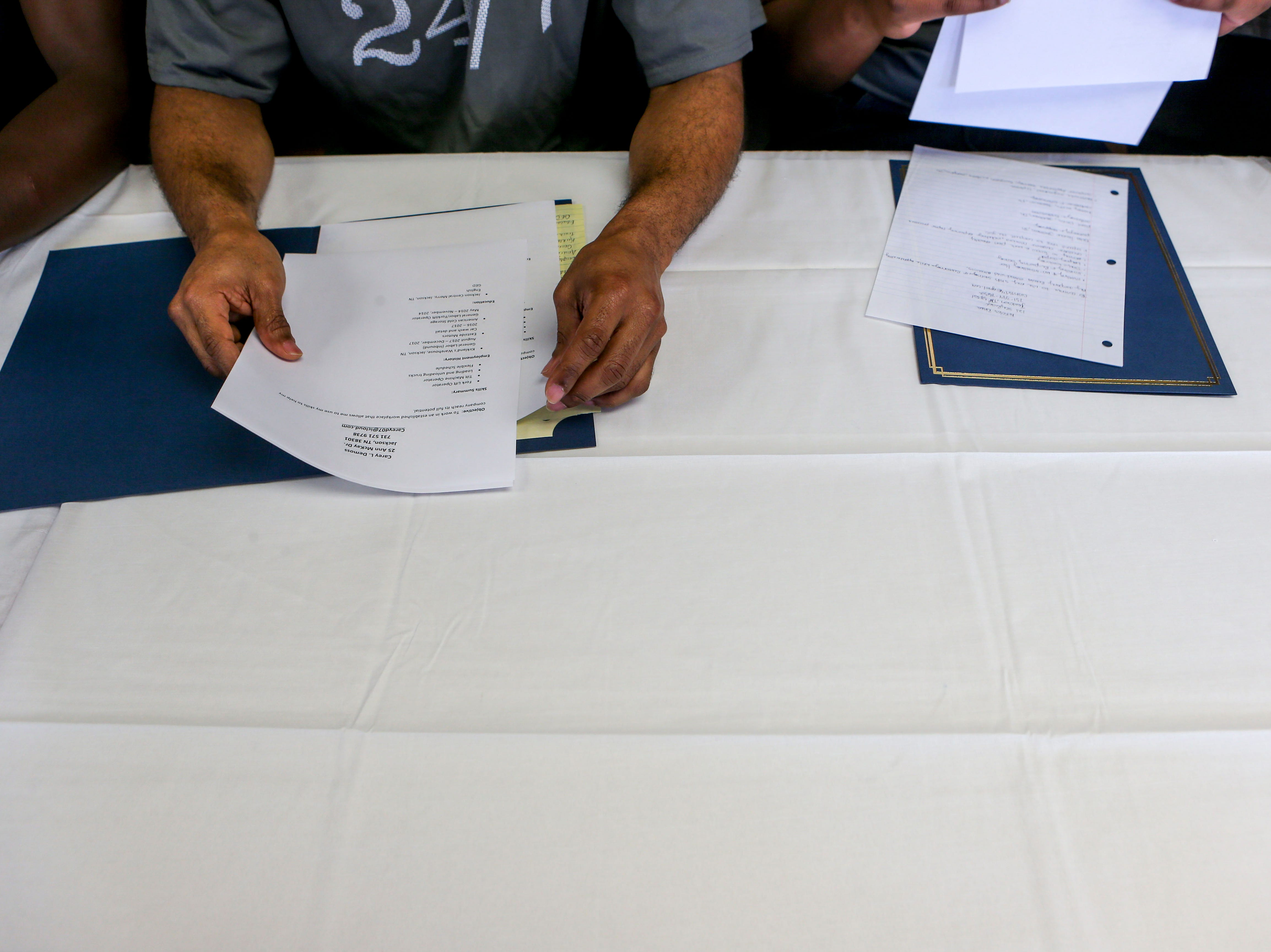 Graduates look over the resumes they were given as a part of the program during a graduation ceremony for the InsideOut Dad program at Madison County Penal Farm in Jackson, Tenn., on Thursday, Oct. 4, 2018.