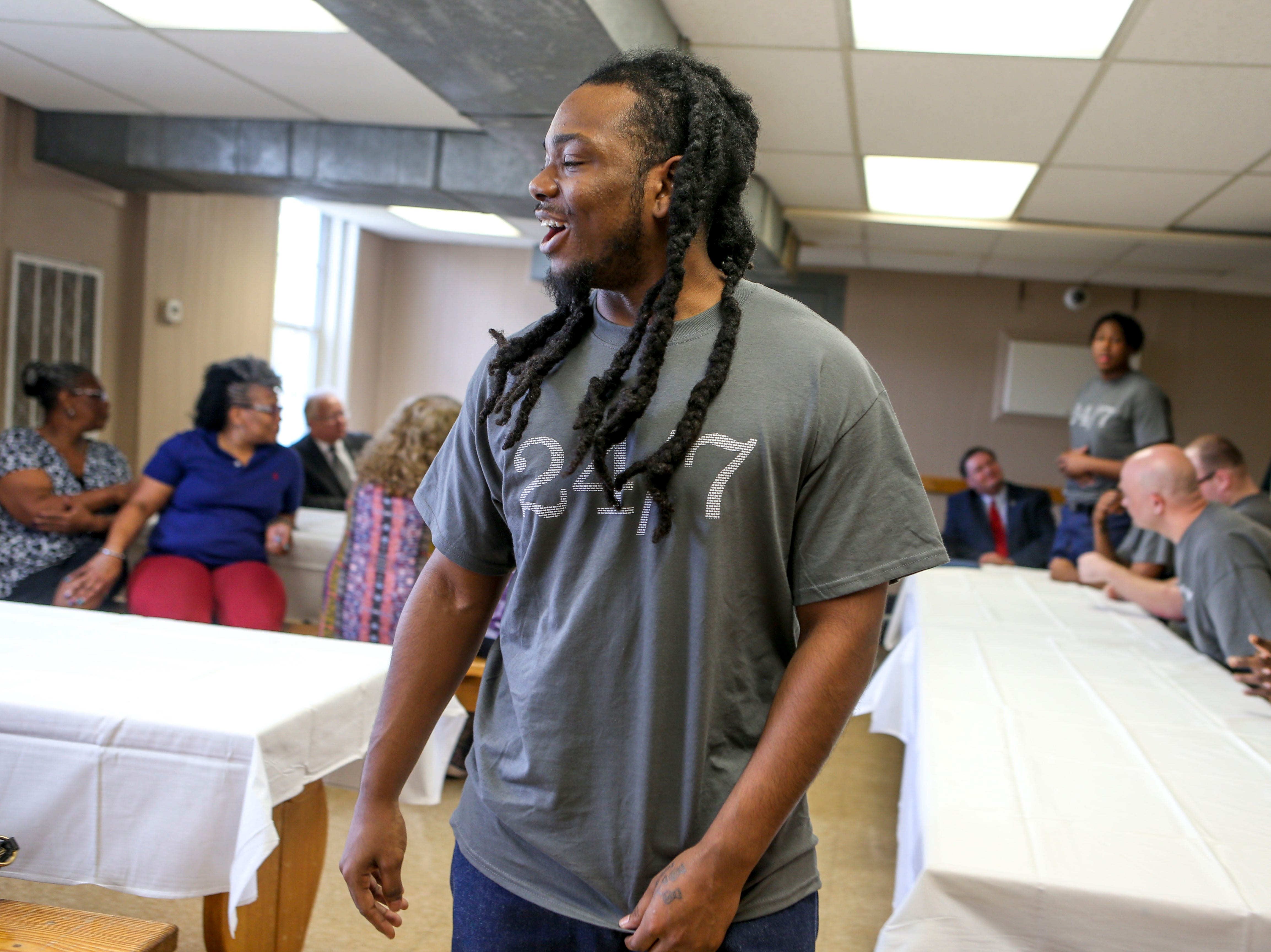 Jarrett Wilson returns to his seat and whispers to his daughter Dreya Wilson during a graduation ceremony for the InsideOut Dad program at Madison County Penal Farm in Jackson, Tenn., on Thursday, Oct. 4, 2018.