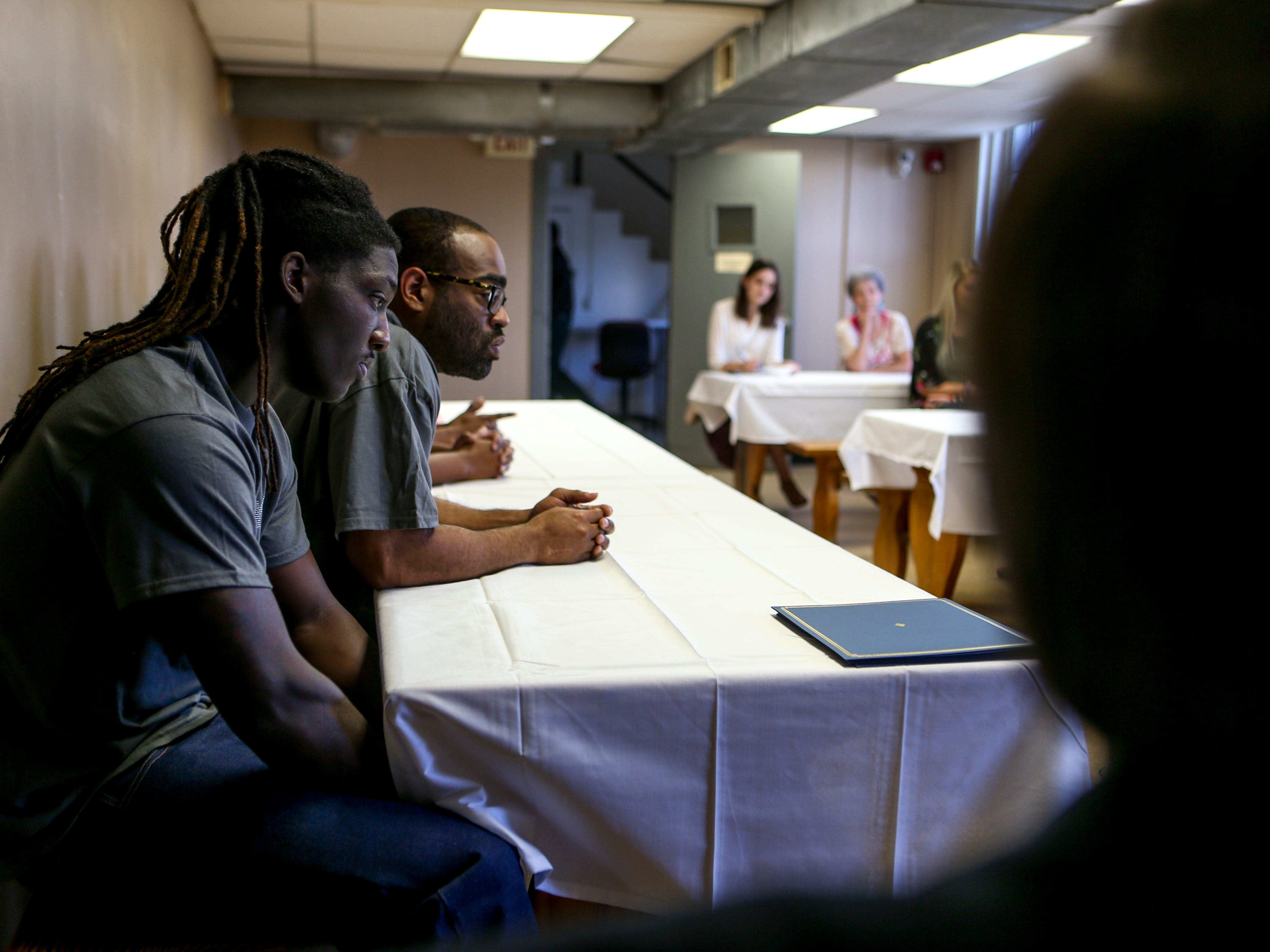 Jarnakin Brown and Carey Demoss listen to program directors speak to those that came in support of graduates during a graduation ceremony for the InsideOut Dad program at Madison County Penal Farm in Jackson, Tenn., on Thursday, Oct. 4, 2018.