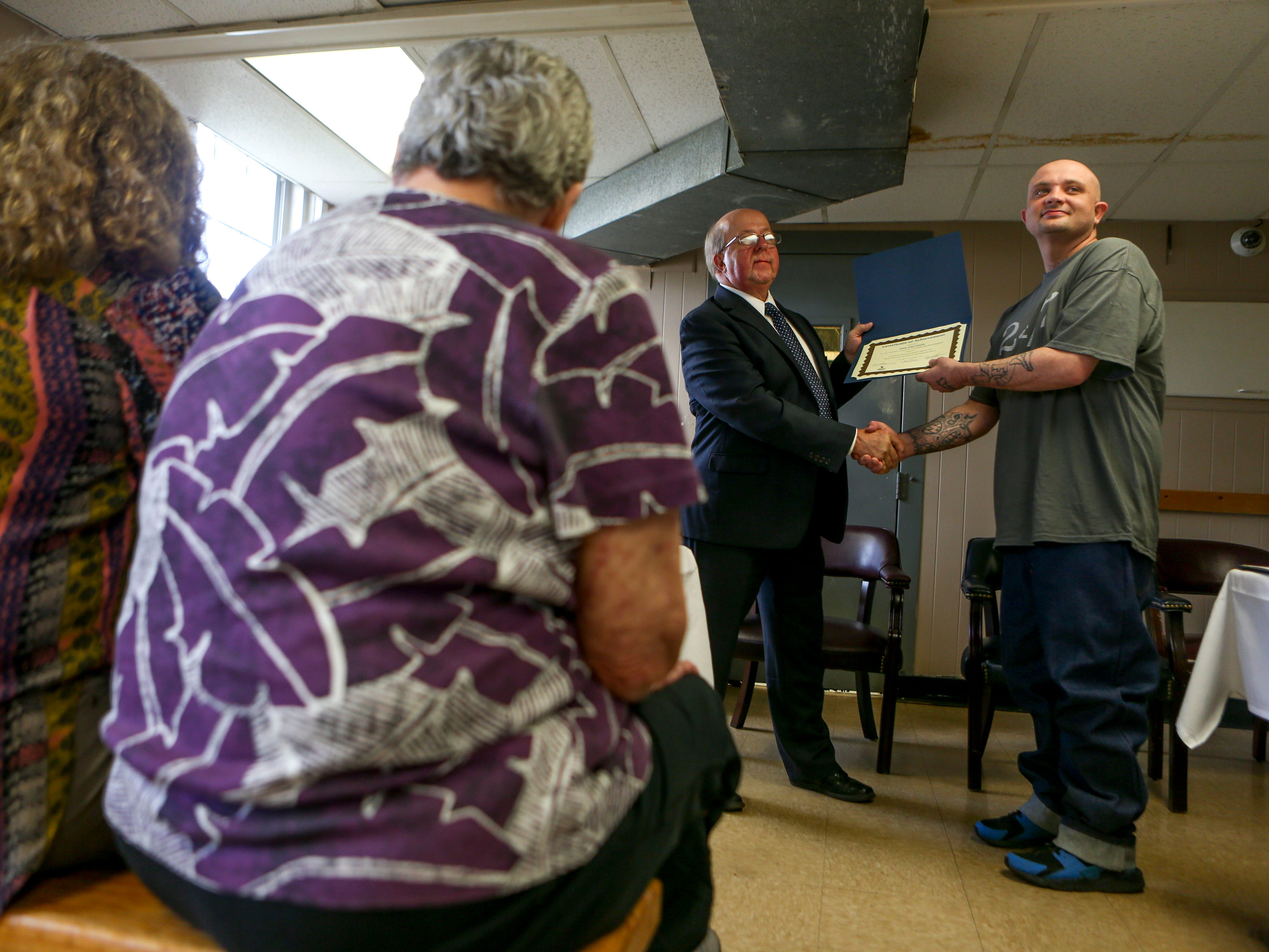 Tim Carothers presents a diploma to Alan Finch during a graduation ceremony for the InsideOut Dad program at Madison County Penal Farm in Jackson, Tenn., on Thursday, Oct. 4, 2018.