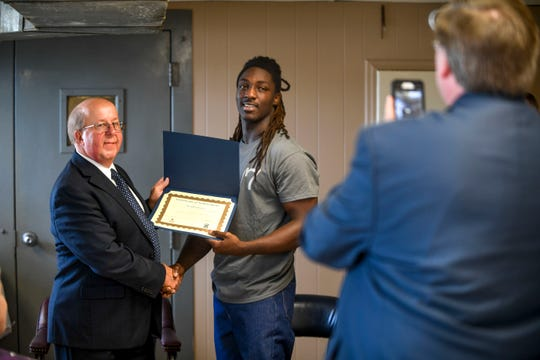 Jarnakin Brown receives his diploma from Tim Carothers during a graduation ceremony for the InsideOut Dad program at Madison County Penal Farm in Jackson, Tenn., on Thursday, Oct. 4, 2018.