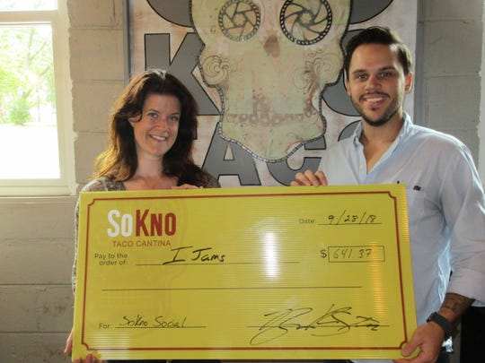 In this file photo, SoKno Taco general manager Ryan Steffy presents Ijams rentals coordinator Carolyn Corley with a check benefiting the nonprofit.