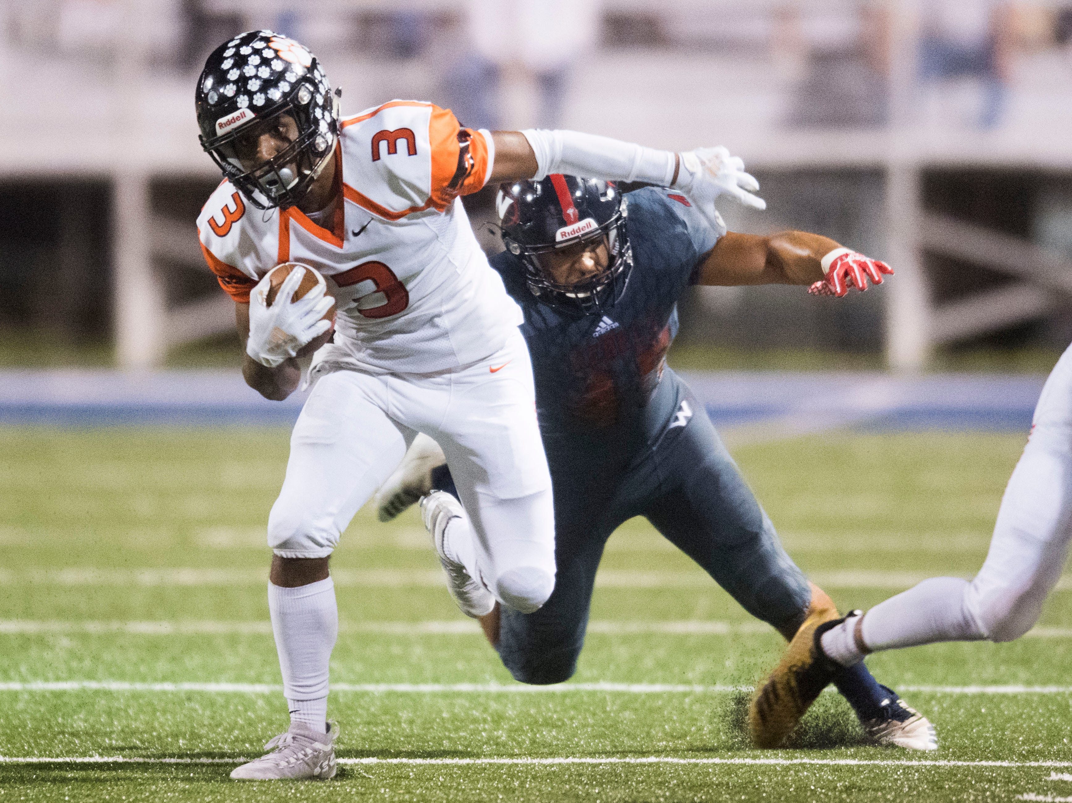 Powell's Bailor Walker (3) runs as West's William Savoy (45) attempts to take hime down during a game between West and Powell at West, Friday, Oct. 5, 2018. Powell defeated West 36-21.