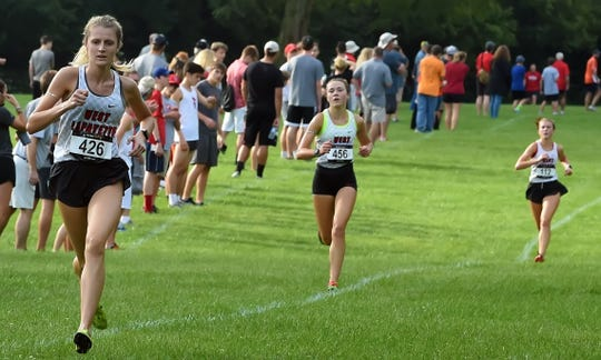 Mary Schultz leads Emma and Ellie Tate into the gate for West Lafayette Saturday in the IHSAA Harrison Cross Country Sectional at the Tippecanoe Amphitheater.
