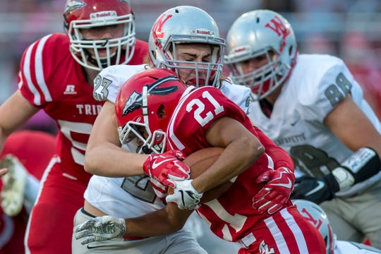 Justin Vasili tackles Zion Cosgray in the first half of the West Lafayette at Twin Lakes football game.