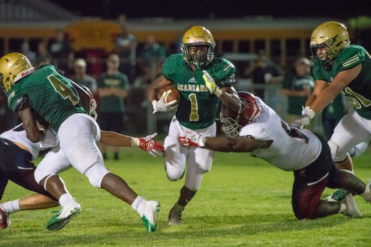 Acadiana's Dillon Monette (1) breaks through a tackle while running the ball down the field against the Comeaux High Spartans last season. Through his first three years on campus, Monette has rushed for 3,510 and is 1,803 yards shy of breaking the school's all-time career rushing record