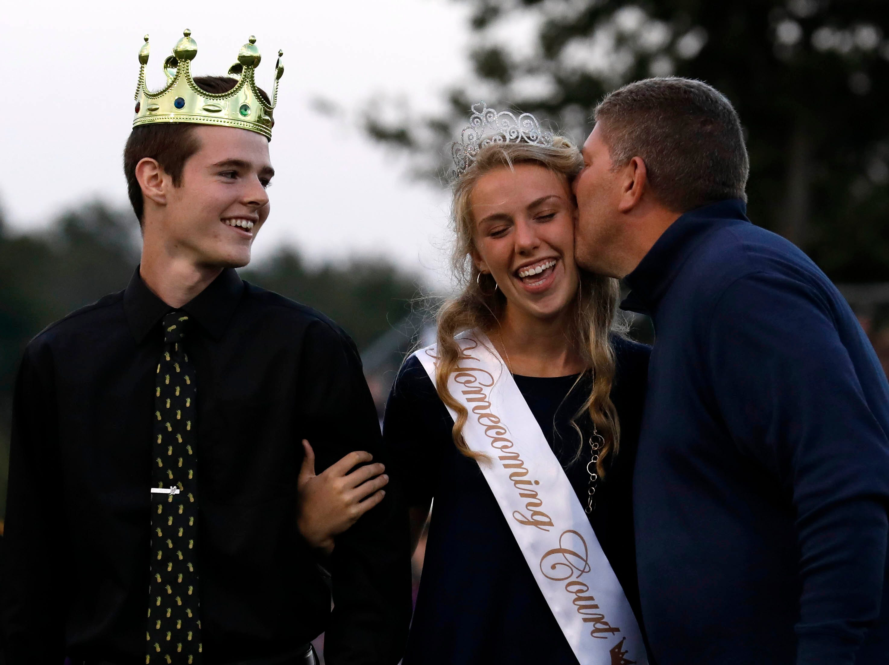 Marty Evaline, right, give his daughter Emaleigh Evaline a kiss on the cheek after she was crowned homecoming queen before Friday night's football game, Oct. 5, 2018, at Bloom-Carroll High School in Carroll.
