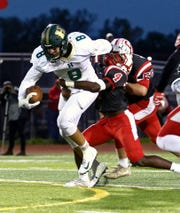 Howell's Michael Brauer tries to escape the grasp of Canton's Steven Walker during the Highlanders' 48-29 loss to the Chiefs on Friday, Oct. 5, 2018.
