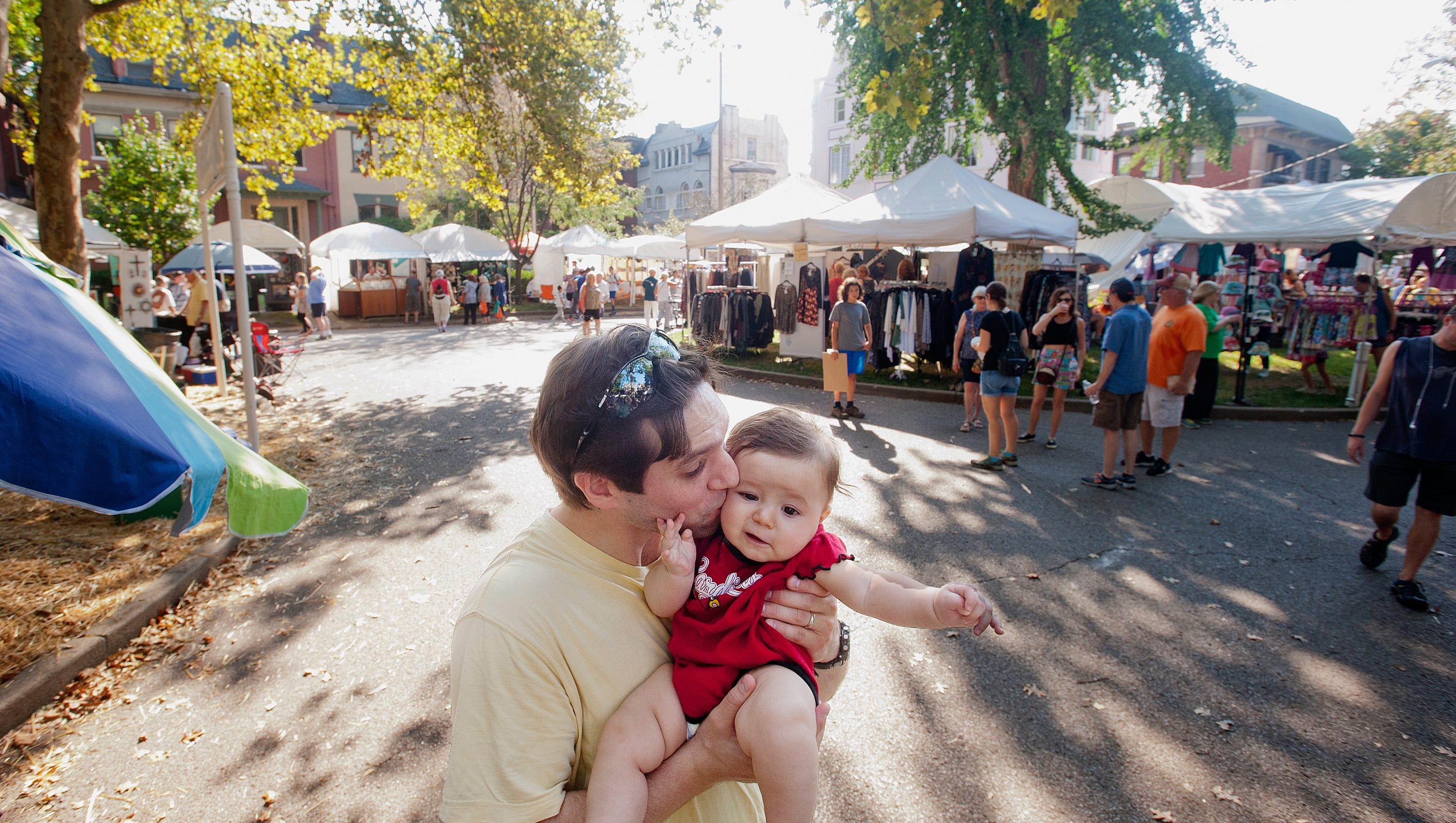 Michael Fazio gives his 6-month-old daughter Isabel a kiss at the St. James Art Fair. The two were taking in the collections of artists' works there. October 06, 2018