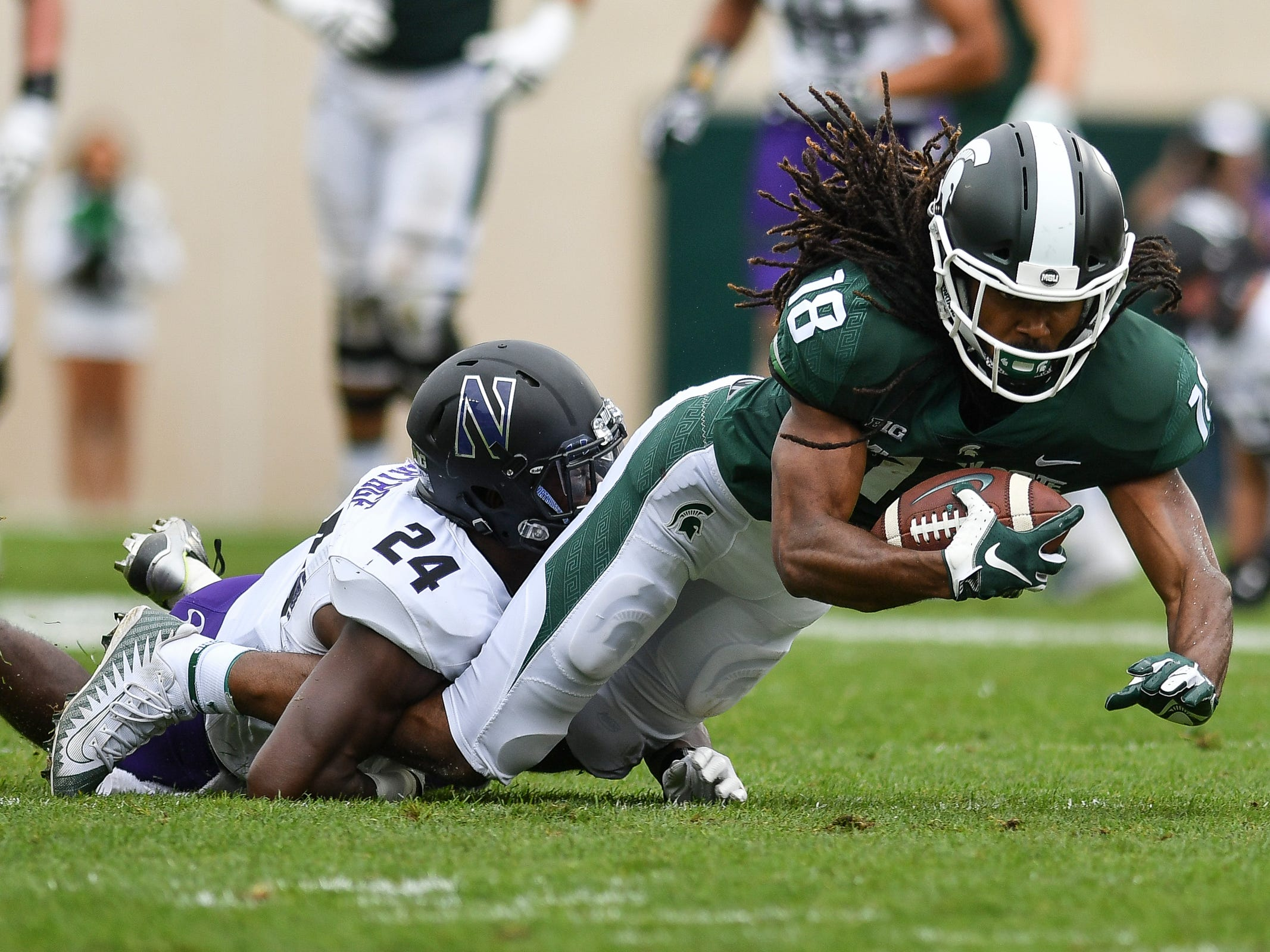MSU's Felton Davis gets tackled by Northwestern's Monte Hartage, Sat., Oct. 6, 2018.