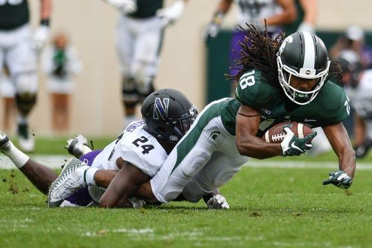 MSU's Felton Davis gets tackled by Northwestern's Monte Hartage, Sat., Oct. 6, 2018.