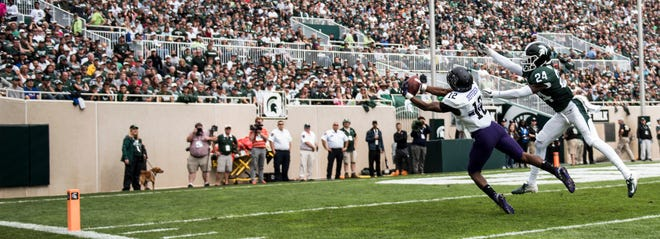 Northwestern's JJ Jefferson snags a pass over MSU's Tre Person for a Northwestern touchdown.