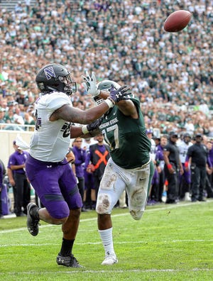 Northwestern Wildcats wide receiver Cameron Green (84) attempts to make a catch behind Michigan State Spartans linebacker Tyriq Thompson (17) during the second half at Spartan Stadium.