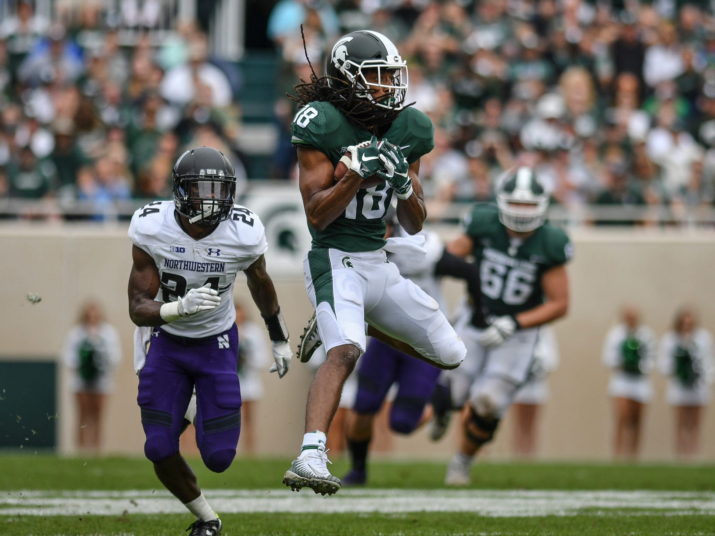 MSU's Felton Davis III gains yardage against Northwestern's Monte Hartage, Sat., Oct 6, 2018.