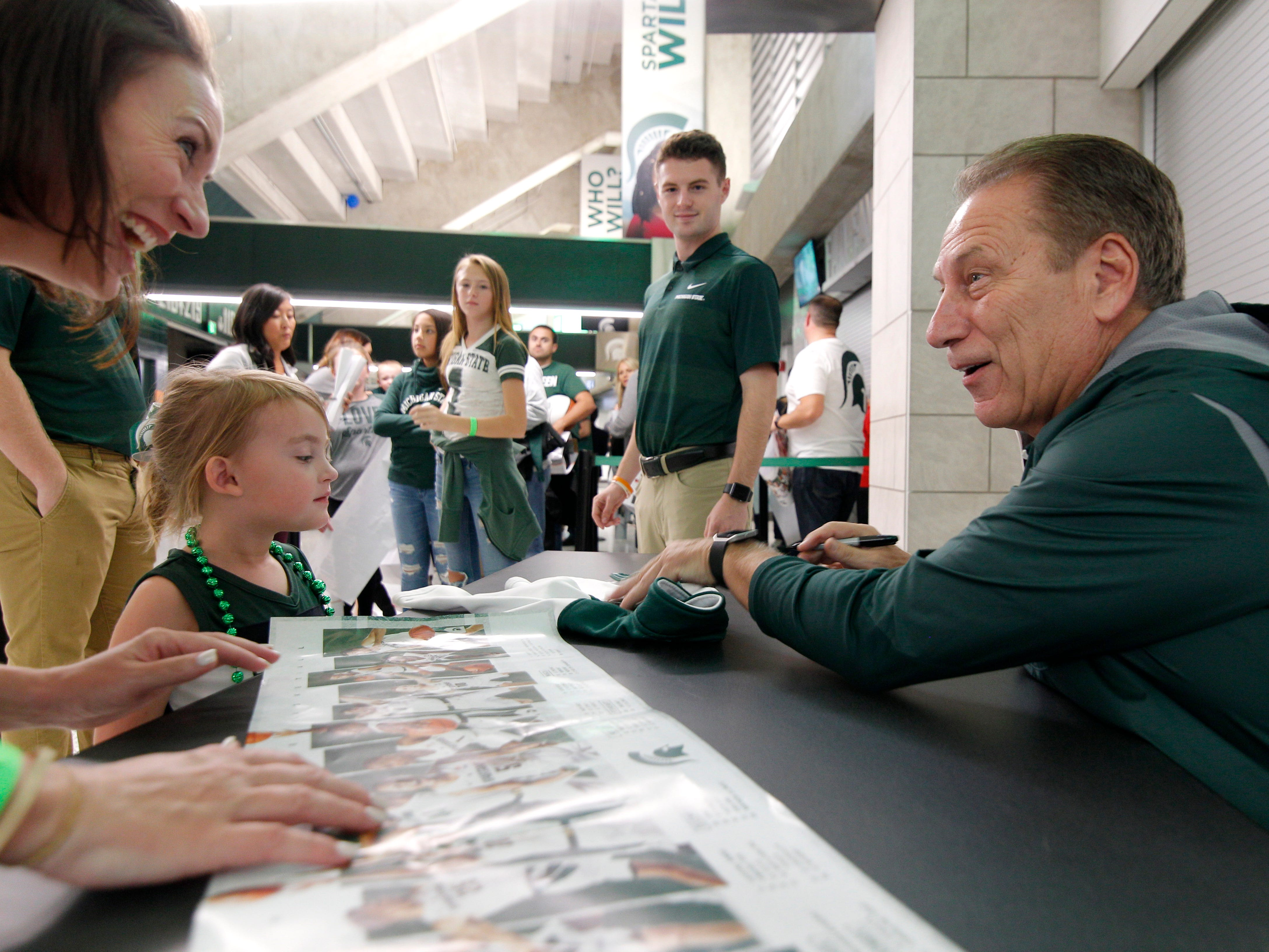 Michigan State men's basketball coach Tom Izzo, right, signs an autograph for Jamie Collins and her daughter Charlotte Collins, 4 at MSU Madness, Friday, Oct. 5, 2018, in East Lansing, Mich.