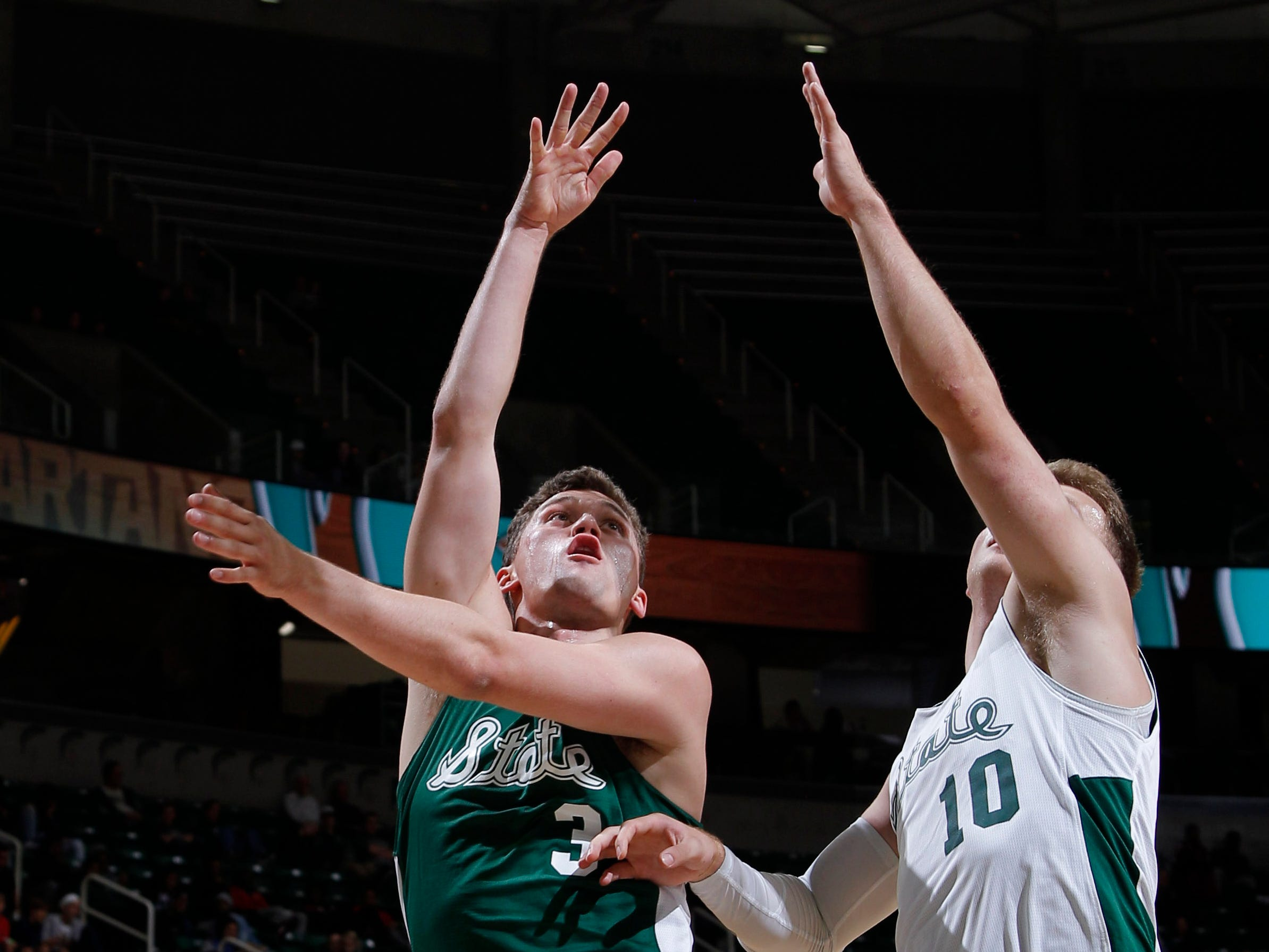 Michigan State's Foster Loyer, left, shoots against Jack Hoiberg at MSU Madness, Saturday, Oct. 6, 2018, in East Lansing, Mich.