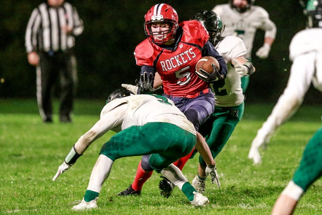 Spencer/Columbus' Ethan Meece(5) attempts to avoid being tackled by Regis' Tristan Root(9), front, and Isaac Michels(12) Friday, Oct. 05, 2018, at Spencer High School football field in Spencer, Wis.