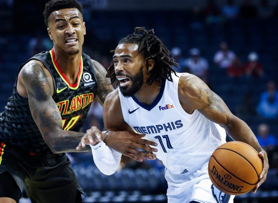 Memphis Grizzlies guard Mike Conley (right) drives the lane against Atlanta Hawks defender Jaylen Adams (left) during first quarter action at the FedExForum in Memphis, Tenn., Friday, October 5, 2018.