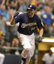 Mike Moustakas gestures toward the Brewers dugout after delivering an RBI single with the bases loaded in the eighth inning against the Rockies to give the Brewers a 2-0 lead during Game 2 on Friday night at Miller Park.