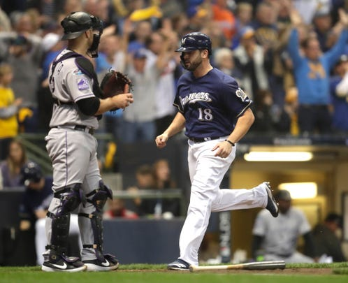 Mike Moustakas crosses home plate in front of Rockies catcher Chris Iannetta with the Brewers' first run of the game in the fourth inning during Game 2 of the teams' NL Division Series on Friday at Miller Park.