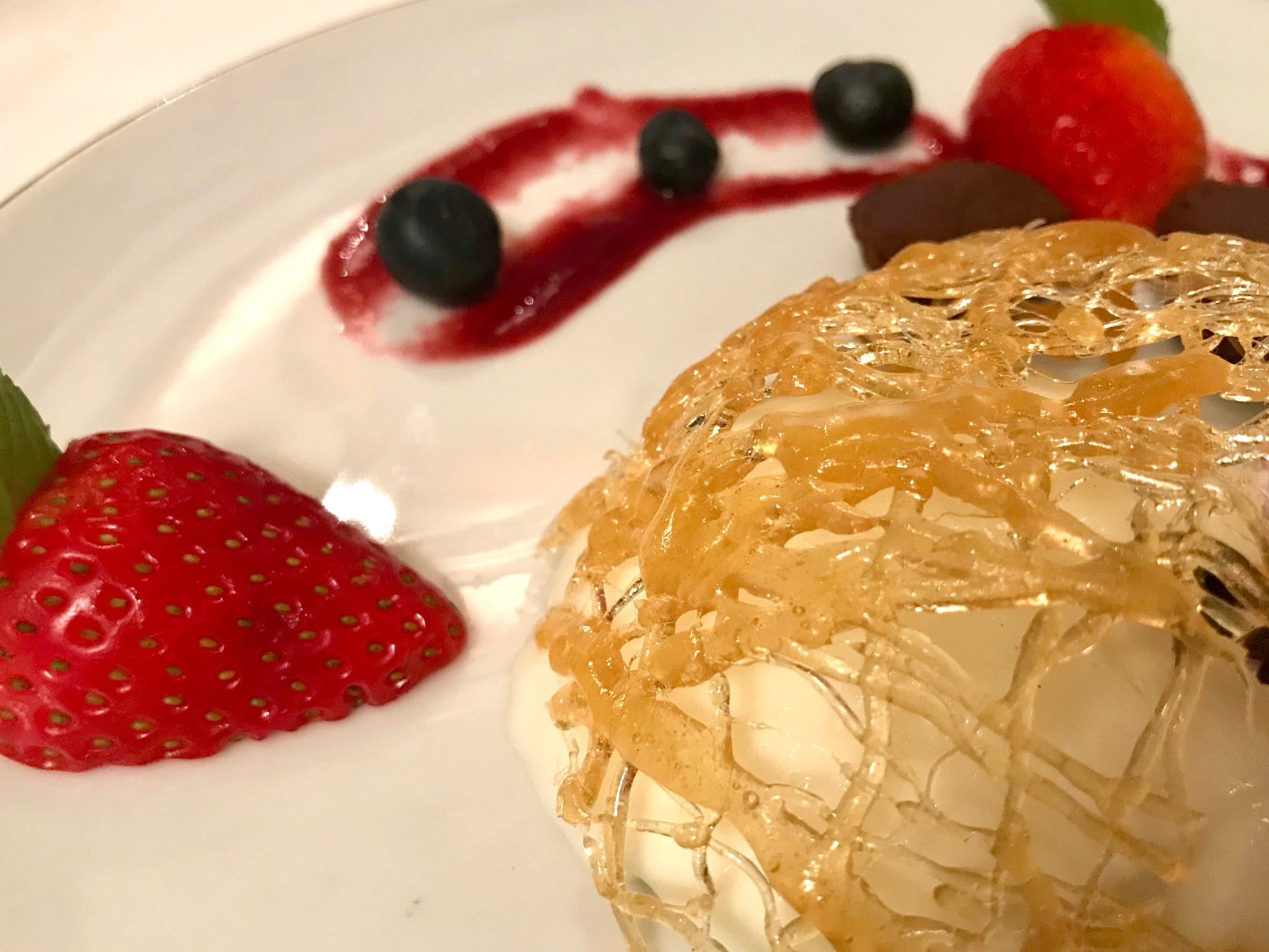 Dessert at Lagniappe Brasserie, 17001 W. Greenfield Ave., New Berlin, might include a rarely seen classic, like this sugar cage. It's set over panna cotta with fresh berries.