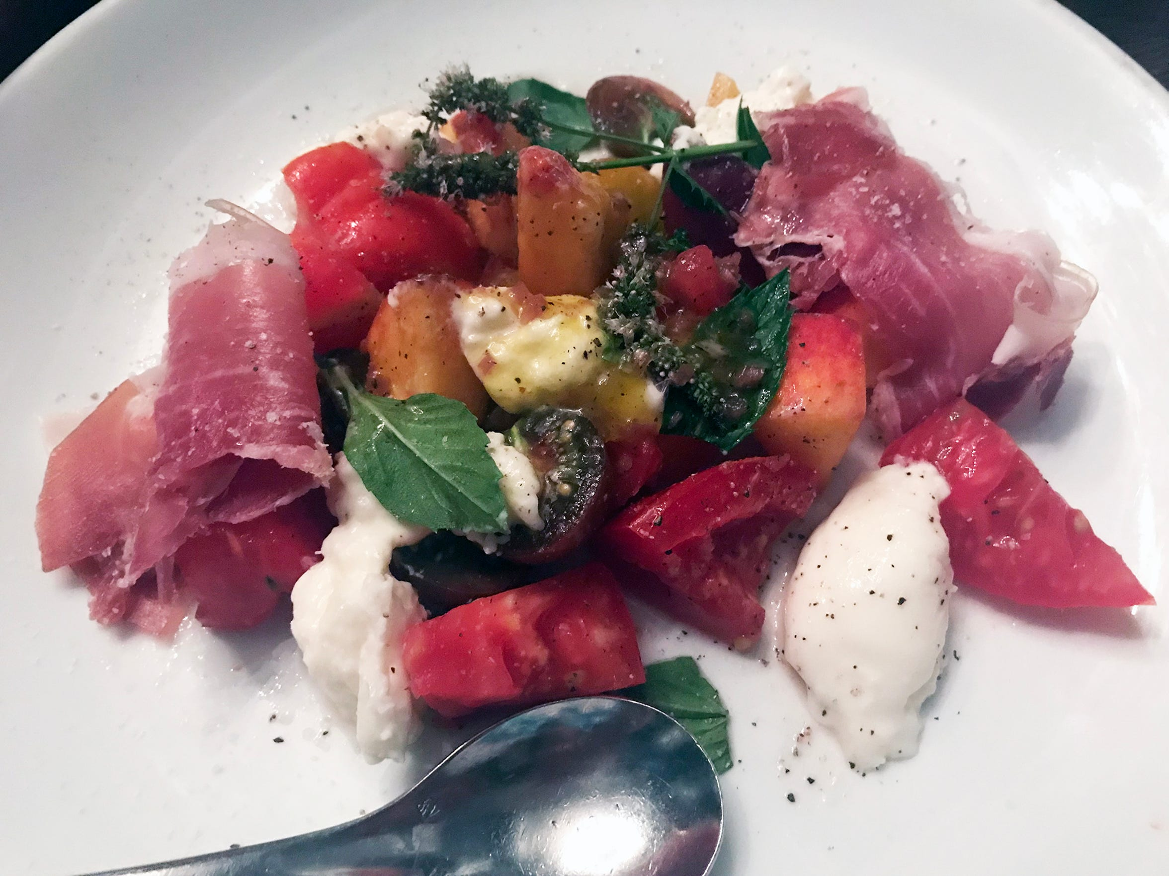 Seasonal ingredients (fresh peaches and tomatoes) meet creamy burrata cheese, prosciutto and fresh herbs in this bright salad at Crazy Water, 839 S. Second St.