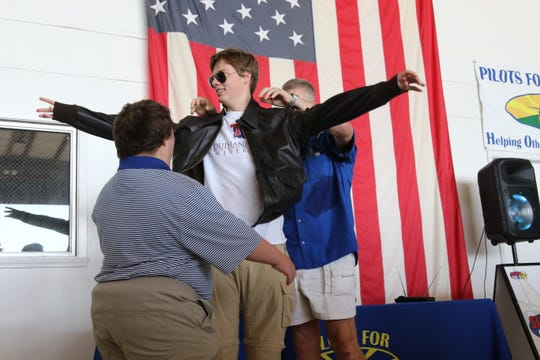 Jeb Andrews, far right, puts a replica of a World War II airman jacket on his son, Mason Andrews, while John James watches on Saturday, Oct. 6, in Monroe, Louisiana. Mason Andrews just completed a solo flight around the world, bringing home three world records.