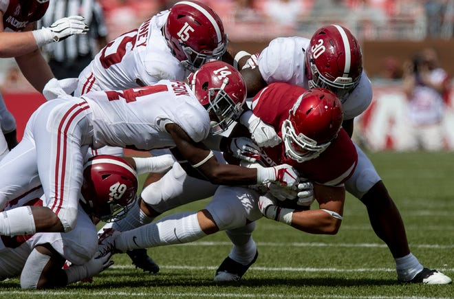 Arkansas tight end Cheyenne O'Grady (85)  is stopped by Alabama linebacker Mack Wilson (30), defensive back Deionte Thompson (14), defensive back Xavier McKinney (15) and defensive lineman Isaiah Buggs (49) during second half action in Fayetteville, Ark., on Saturday October 6, 2018.