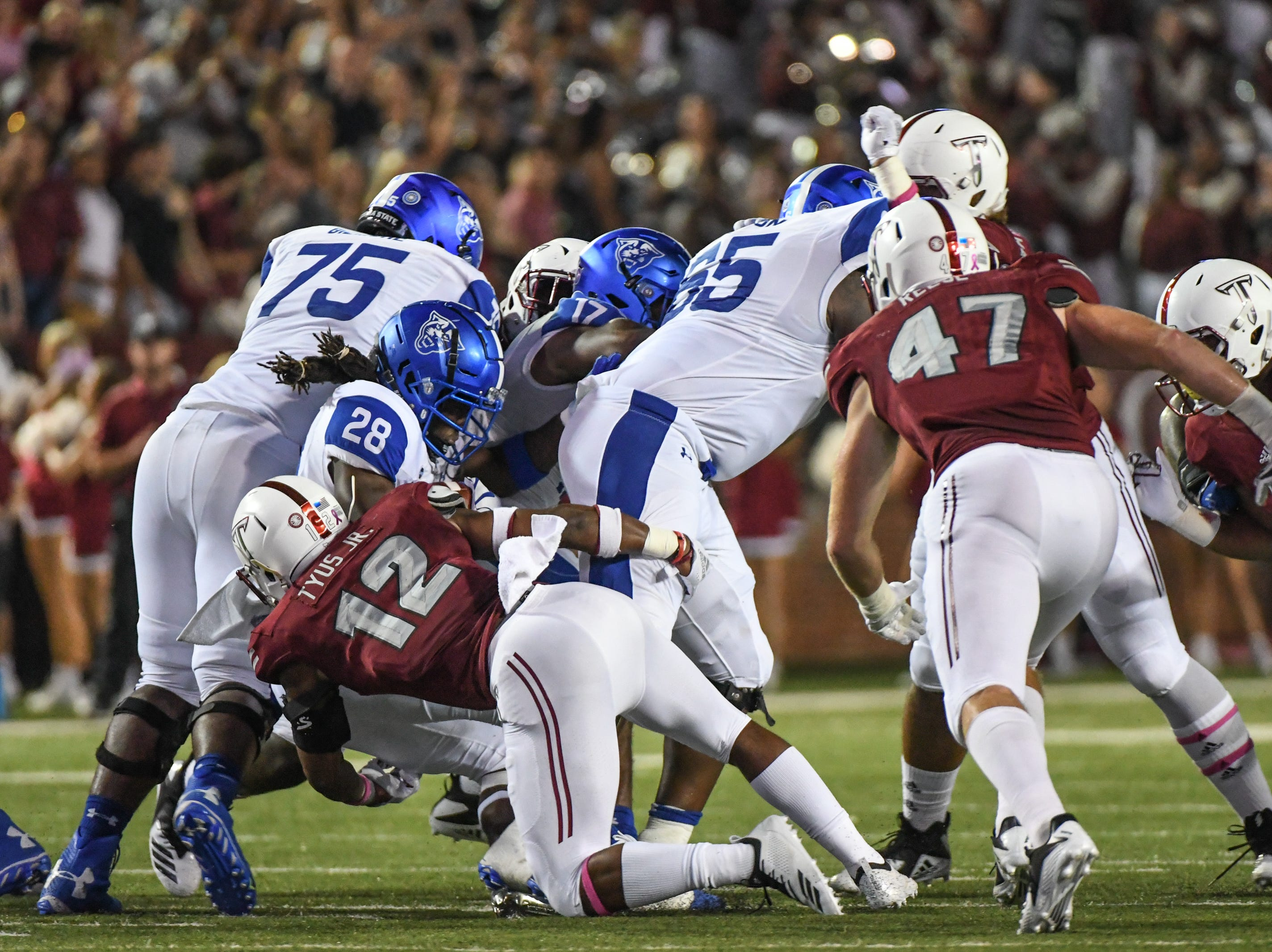 Georgia State Panthers running back Seth Paige (28) is tackled by Troy Trojans safety Melvin Tyus (12)  at Veteran's Memorial Stadium in Troy, Ala., on Thursday, Oct. 4, 2018. (Chip Dillard/Special to the Montgomery Advertiser)