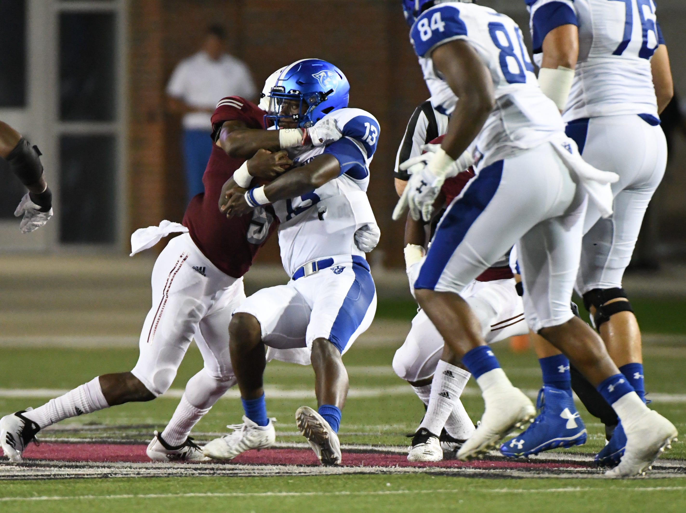 Georgia State Panthers quarterback Dan Ellington (13) is tackled by Troy Trojans safety Cedarius Rookard (5) at Veteran's Memorial Stadium in Troy, Ala., on Thursday, Oct. 4, 2018. (Chip Dillard/Special to the Montgomery Advertiser)