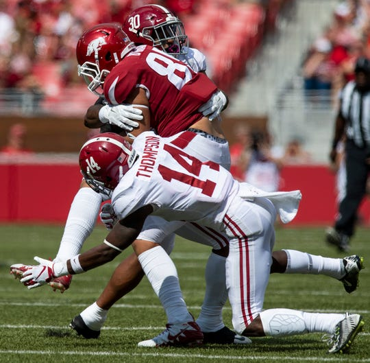 Alabama defensive back Deionte Thompson (14) and Alabama linebacker Mack Wilson (30) hit Arkansas wide receiver Peyton Ausley (84) during second half action in Fayetteville, Ark., on Saturday October 6, 2018.