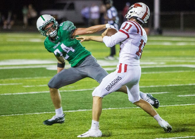 New Castle's Nicholas Grieser tries to bring down New Palestine QB Zach Neligh at New Castle High School Friday, Oct. 5, 2018.