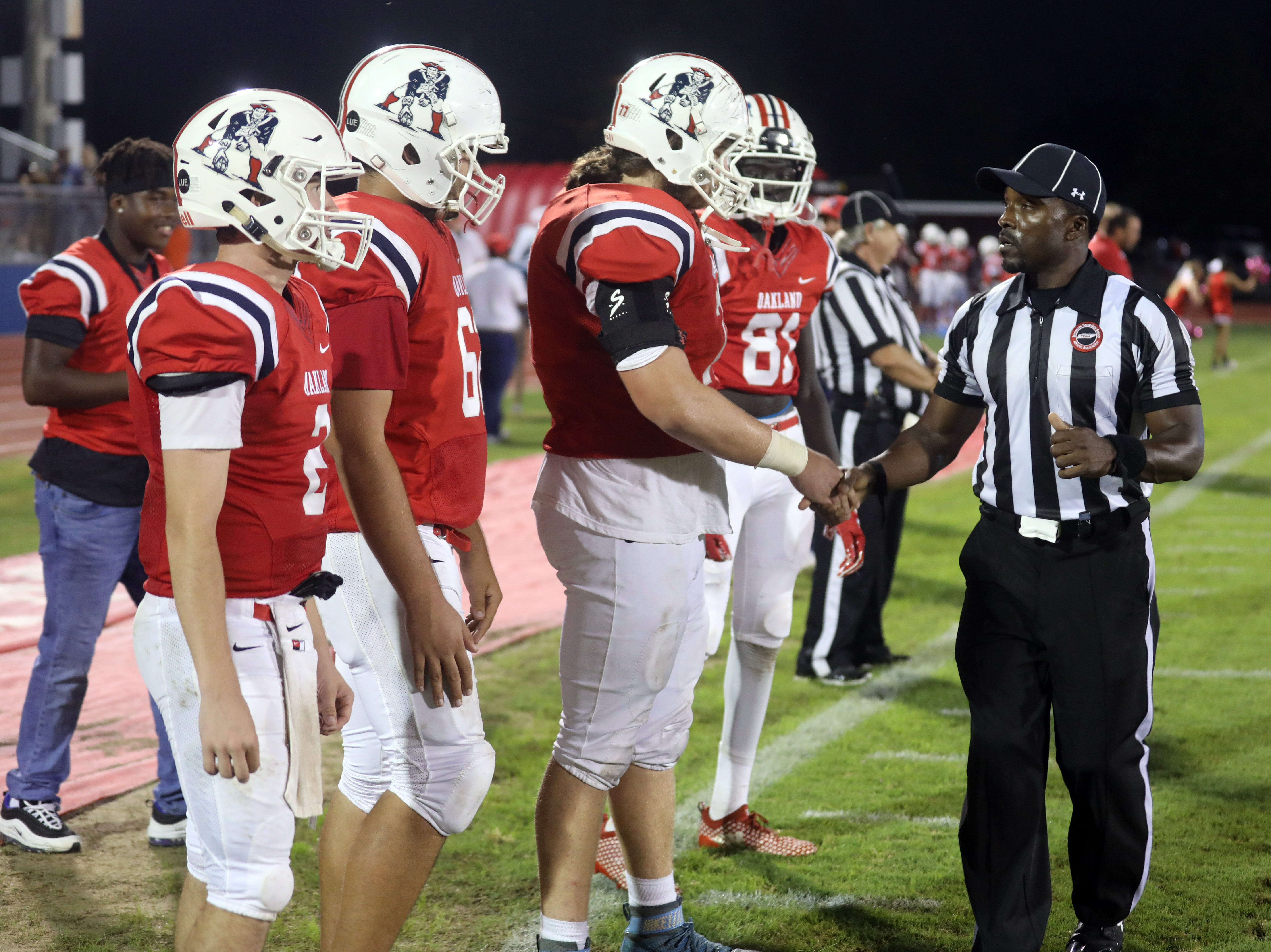A ref greets Oakland players before the start of their game against Franklin at Oakland High School in Murfreesboro Friday October 5, 2018.