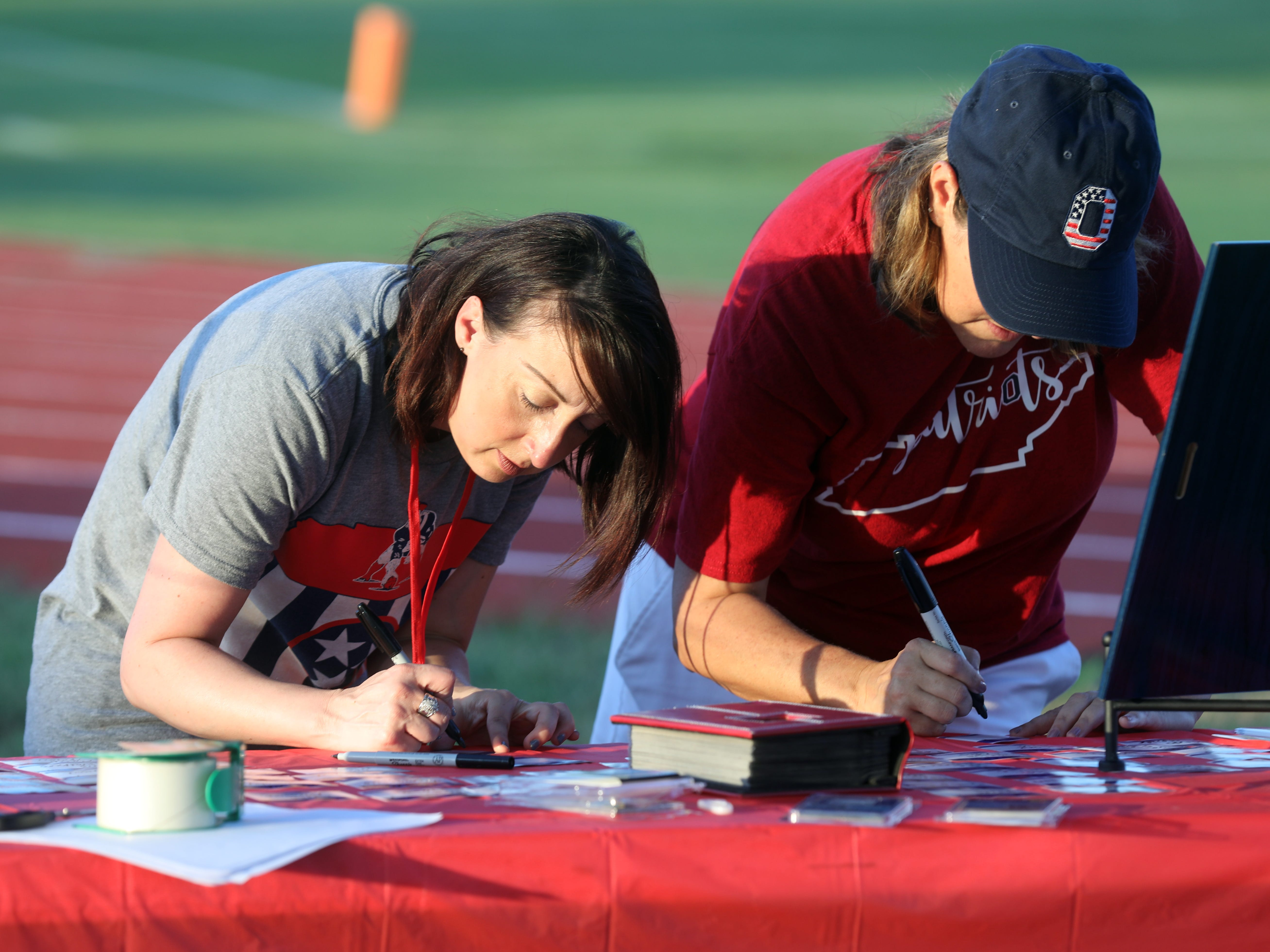 Jamie Moorehead, left, and Pam Curray, right, fill out name tags for the 2008 Oakland High School football team who are to honored during the game at Oakland High School in Murfreesboro Friday, October 5, 2018.