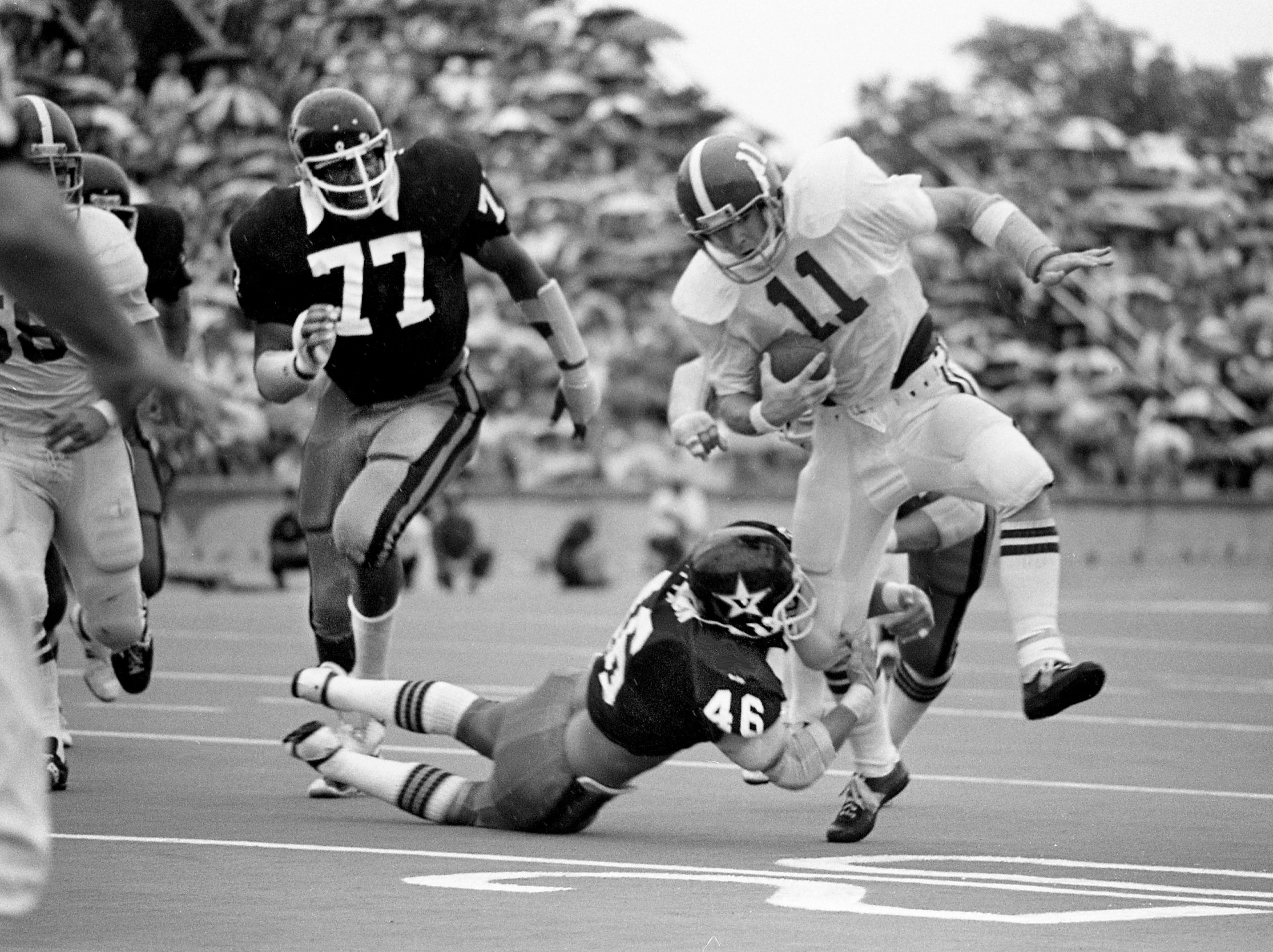 Alabama quarterback Jeff Rutledge (11) is getting grabbed by Vanderbilt linebacker Randy Sittason (46) as Sittason's teammate Dennis Harrison (77) moves in. The Crimson Tide won 24-12 over the Commodores at Dudley Field Sept. 24, 1977.