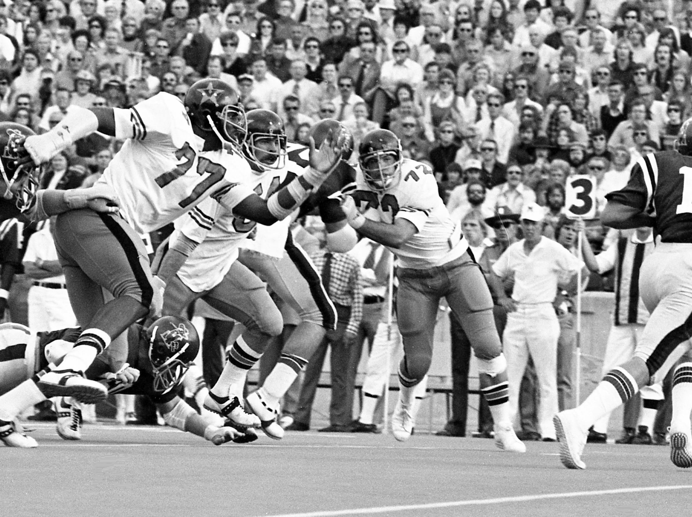 Vanderbilt defensive lineman Dennis Harrison (77) gets by his blocker and head after Ole Miss quarterback Guy Evans (15) in the Commodores 24-14 victory Oct. 26, 1974.