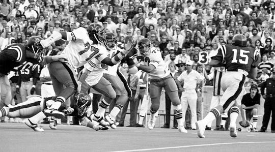 Vanderbilt defensive lineman Dennis Harrison (77) gets by his blocker and heads after Ole Miss quarterback Guy Evans (15) during a 1974 game.